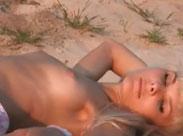 Süsse junge Blondine räkelt sich am Strand