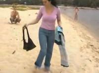 Schwarzhaarige ist nackt am Strand